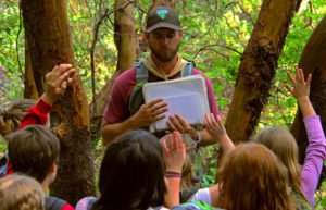 Man holding notebook in front of kids in the woods