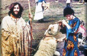 Young hippies playing flute with sheep in Vermont