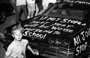 Boy with American flag beside car with graffiti