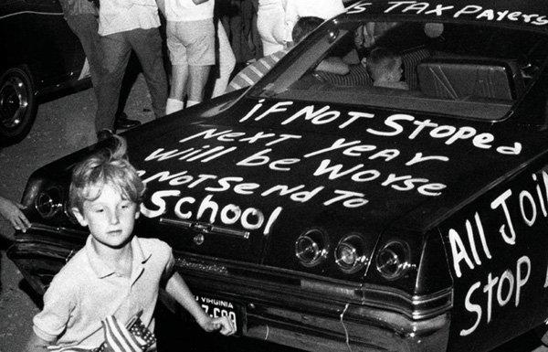 Boy with American flag beside car with graffiti