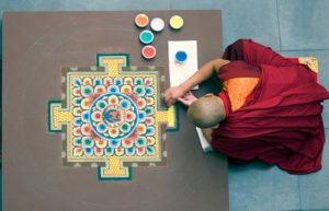 Buddhist monk creating sand painting