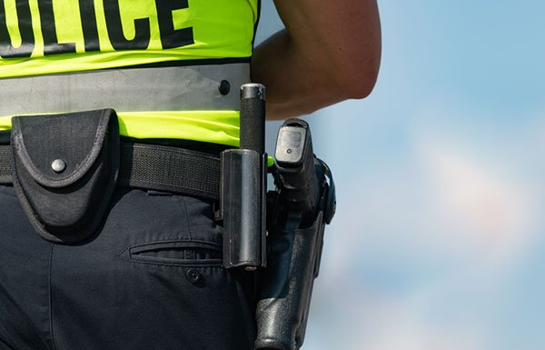 Policeman from behind with close up of holster