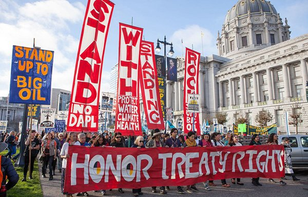 "Protesters marching with ""Honor Treaty Rights"" banner"