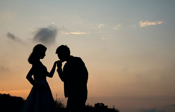 Silhouette of couple kissing in front of cityscape