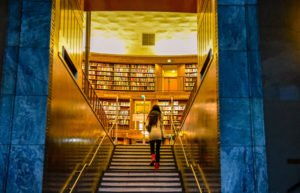 Young woman walking into lit-up library building