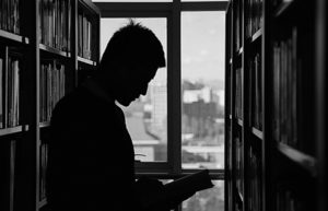 Silhouette of man reading library book in stacks