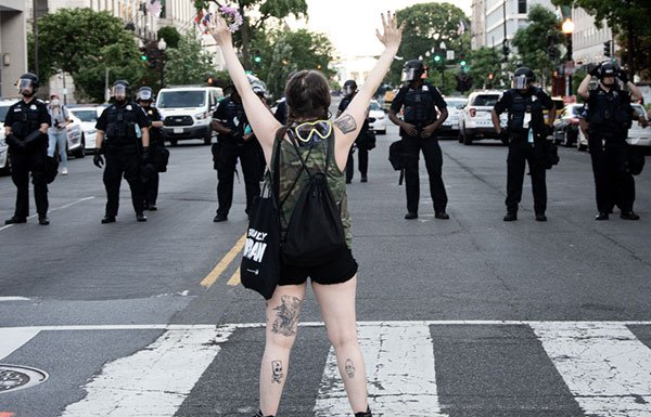 Young woman with hands out in front of line of police