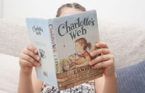 Young girl reading EB White's Charlotte's Web