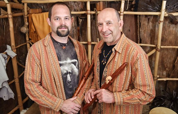 Joseph and Jesse Bruchac holding flutes in traditional Abenaki structure