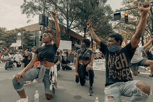 Group of teenage protesters kneeling in Charlotte, NC