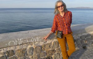 """Poet Verandah Porche in a red top and orange pants pointing at """"one love"""" graffiti on a waterfront wall"""