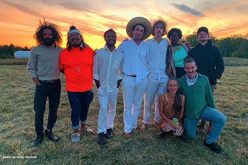 Group of performers standing with arms around each other on a Vermont field.