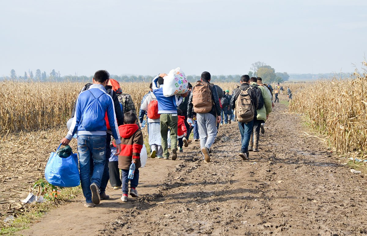 Group of refugees walking through a dry corn field