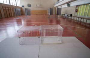 Glass ballot box on a table in a school gymnasium