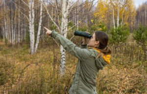 Young woman in green jacket pointing in the woods while holding binoculars