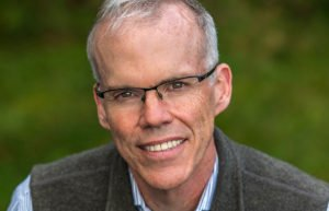 Author Bill McKibben wearing glasses, a blue shirt, and a vest