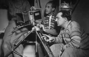 Director Fritz Lang looking at a film camera on a tripod