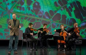 Physicist Dr. Robert Davies of Utah State University with the Fry Street Quartet in front of a green close-up of a leaf