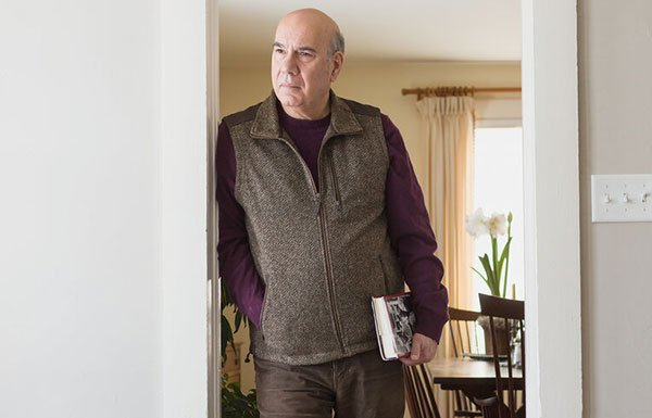 Poet Jay Parini, in a brown vest, leaning on a door frame inside a house