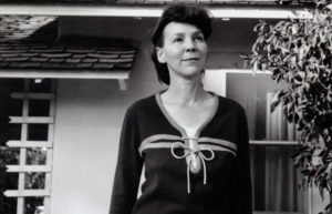 Poet Ruth Stone in a black dress outside of a bungalow