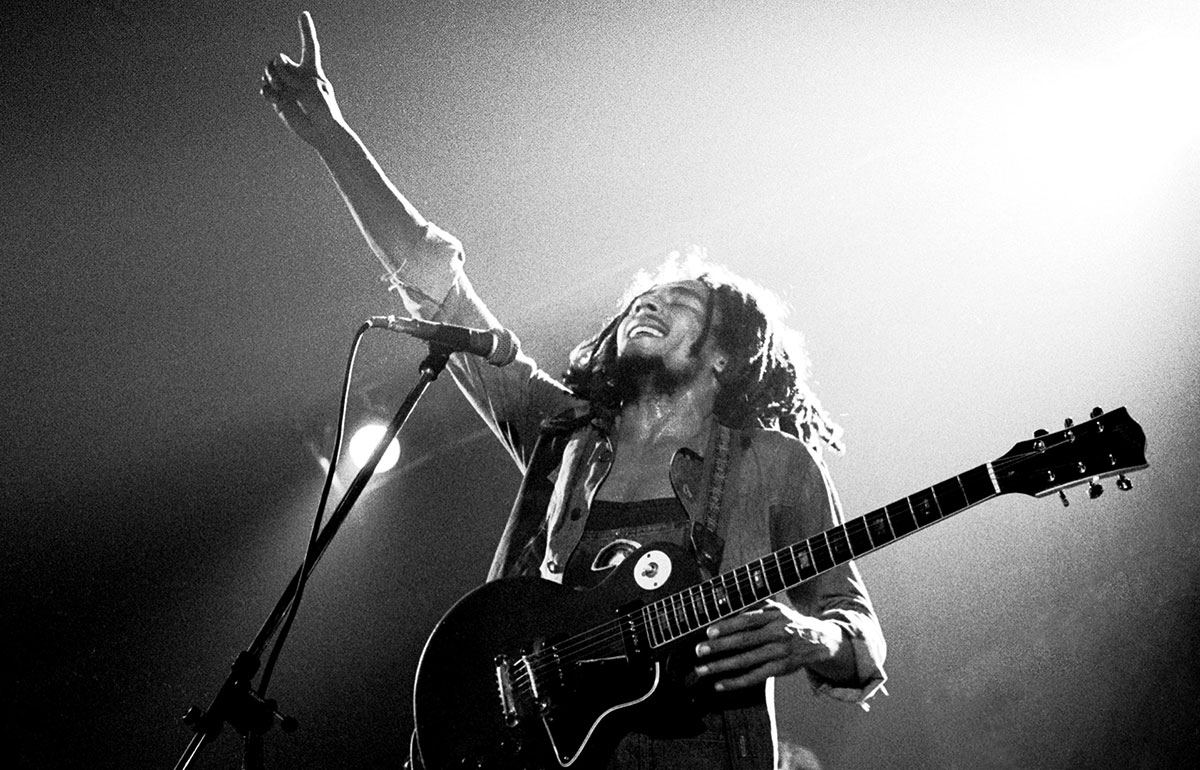Musician Bob Marley holding a guitar and pointing skyward during a concert.