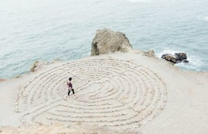 Woman walking through a maze in stones on a cliff edge