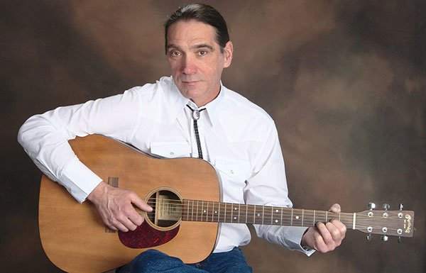 Singer-songwriter Bryan Blanchetter in a white short with a bolo tie, holding a guitar, sitting against a brown background