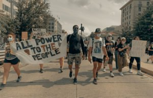 """Diverse group of young marchers in city with """"All Power to the People"""" banner"""
