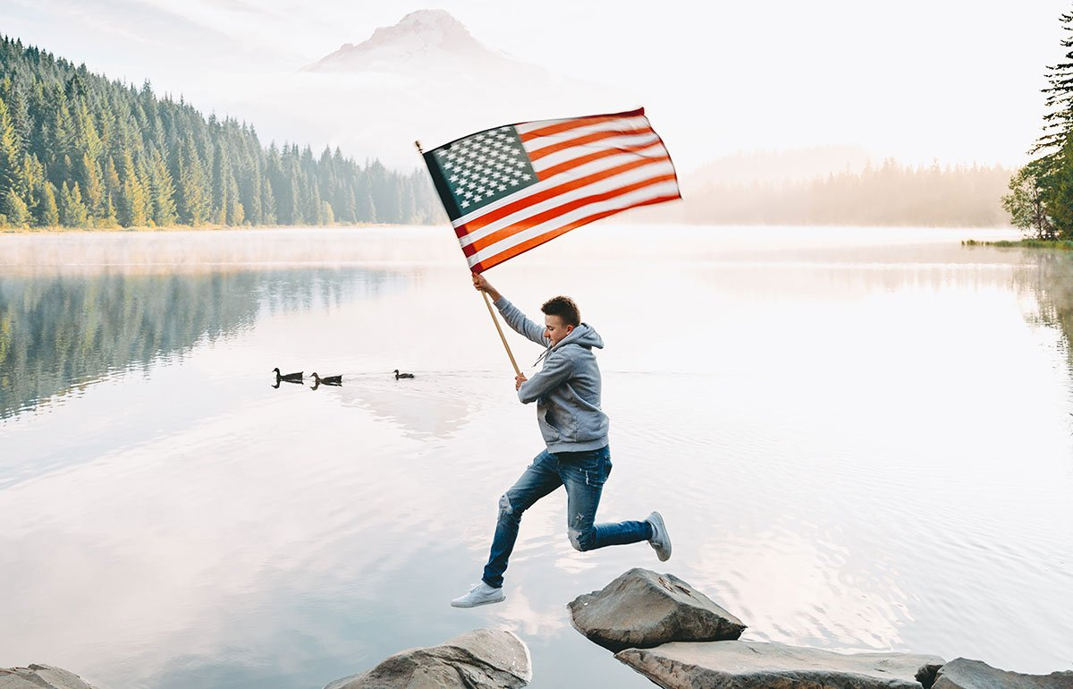 Young man holding an American flag jumping between rocks in a river