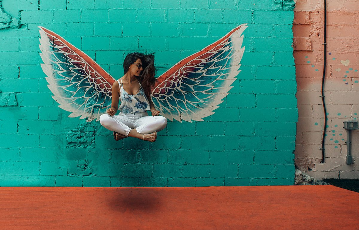 Young woman seated cross-legged in front of wall with wings painted on it