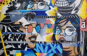 Young man and young woman's faces on a wall of graffiti