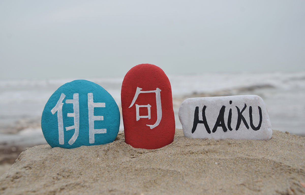 """Three stones standing in sand, one with """"haiku"""" painted on it in black letters"""