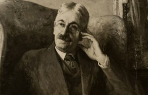 Portrait of John Dewey sitting in a chair, hand at his temple