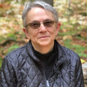 Judy Chalmer wearing glasses and a black jacket seated in the fall woodss