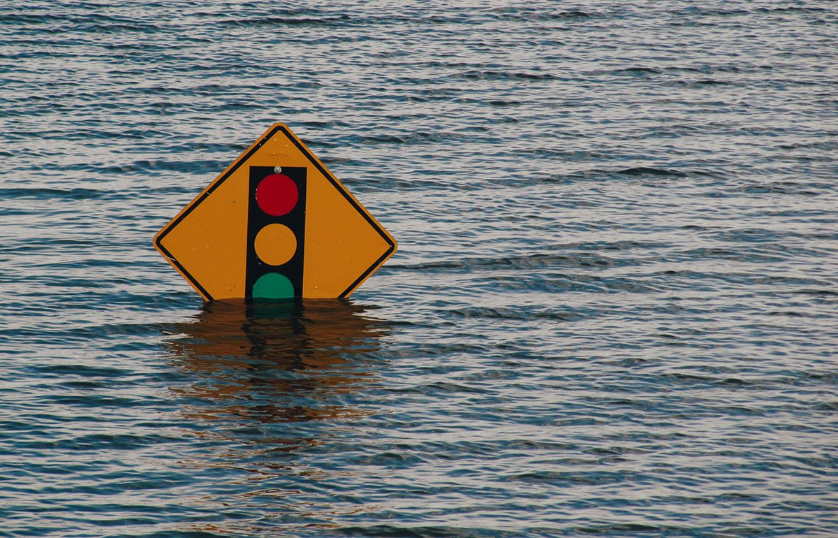 Stop light sign partly submerged in water