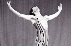 Dancer with arms spread wide, wearing a striped leotard