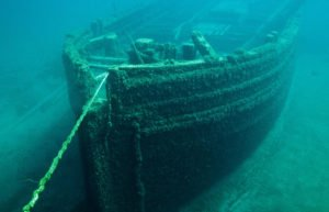 Image of boat under green water with a rope tied around the bow