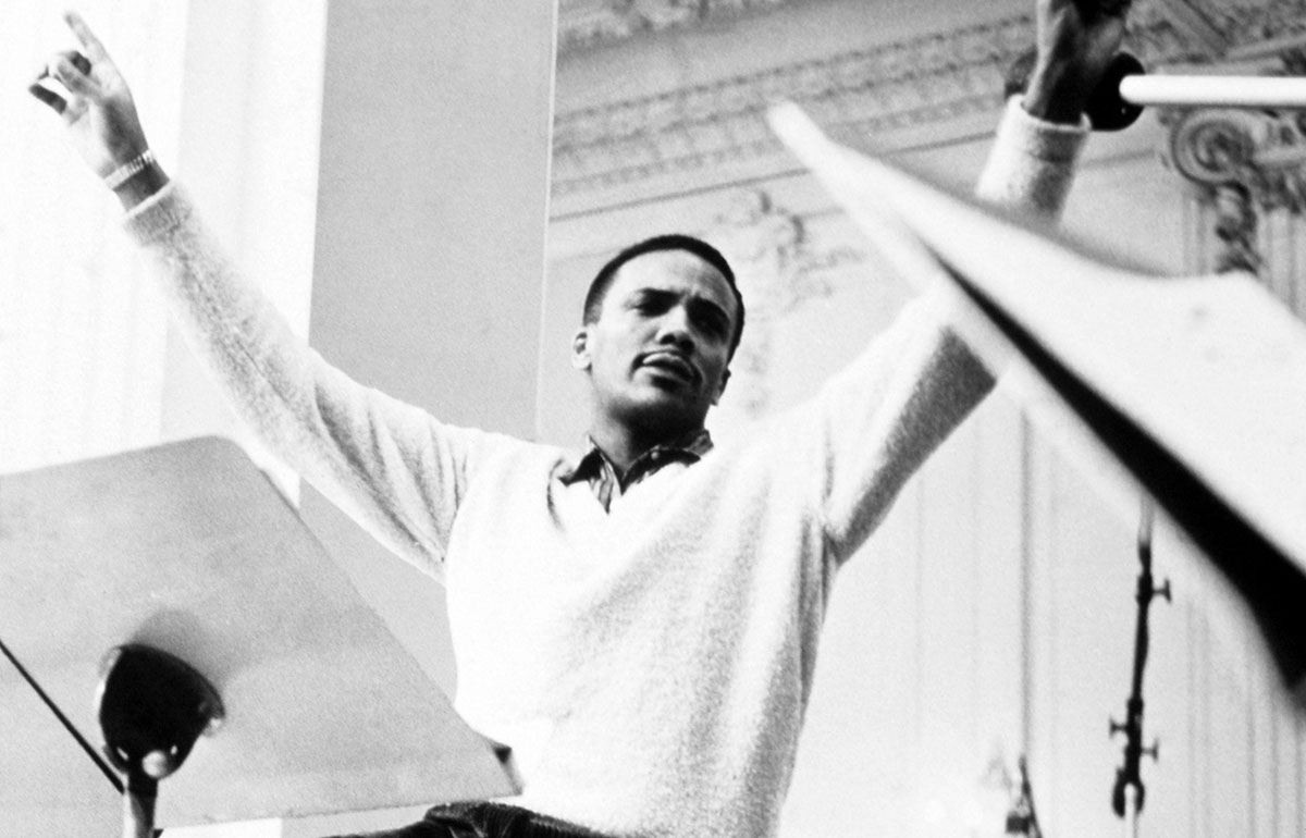 Composer Quincy Jones gesturing while leading an orchestra