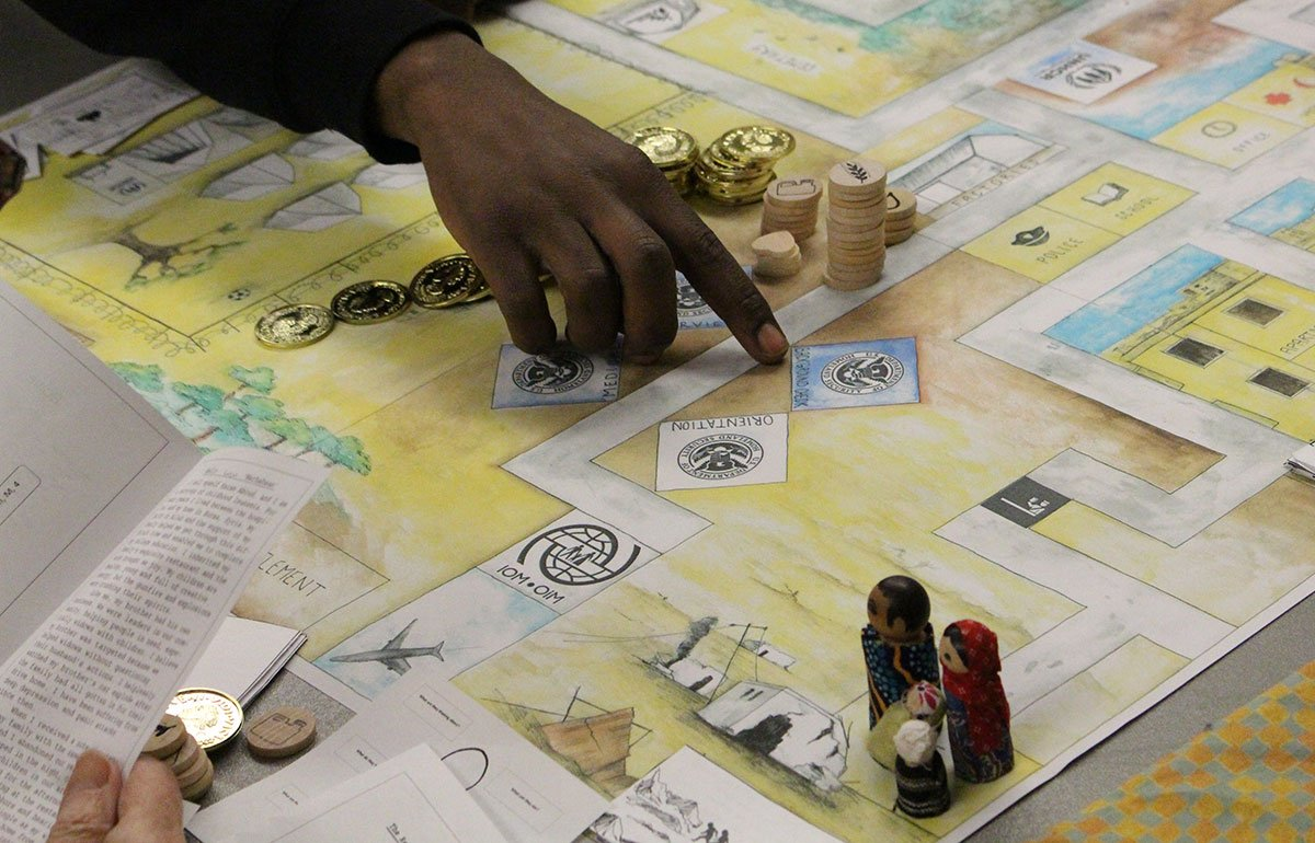 Hand pointing to a space on the Refugee Journey game board