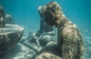 Two underwater statues with moss growing over them