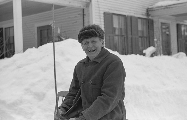 Vermont farmer sitting on snow bank laughing