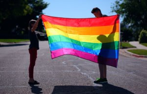 Two young people on a suburban street unfurling a rainbow Pride flag