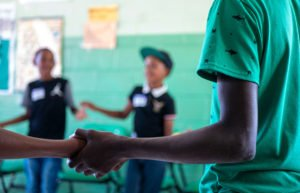 Boys holding hands in a circle in a classroom with green walls
