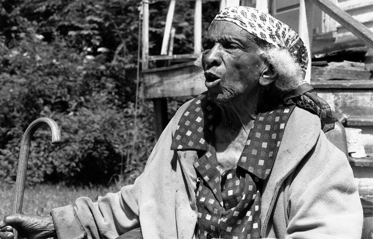 Daisy Turner in a headscarf with a cane in front of her Vermont home