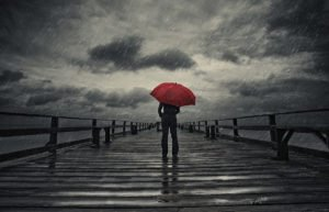 Person with a red umbrella standing on a dock in the rain