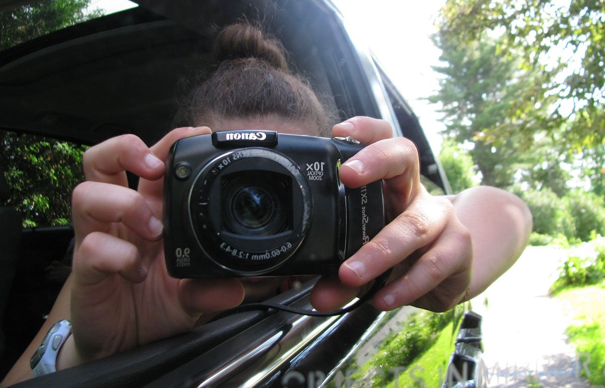 Teenager taking a photo in a care mirror with a digital camera