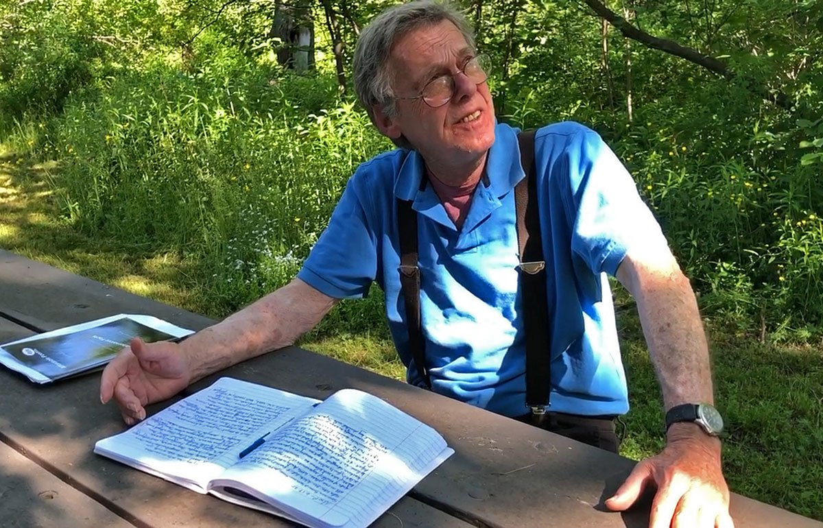Poet Geof Hewitt seated at a picnic table with a book, looking up