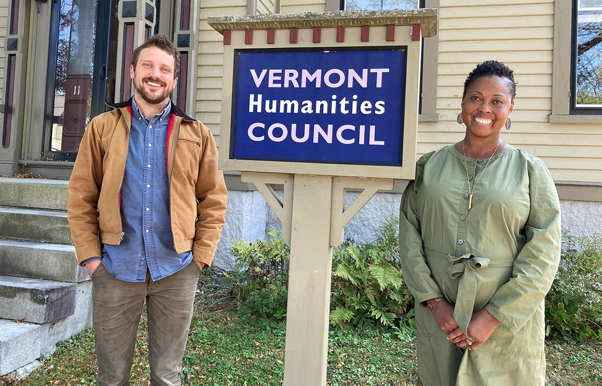 Staffers Jonny Flood and Rachel Edens in front of the Vermont Humanities sign in front of the building
