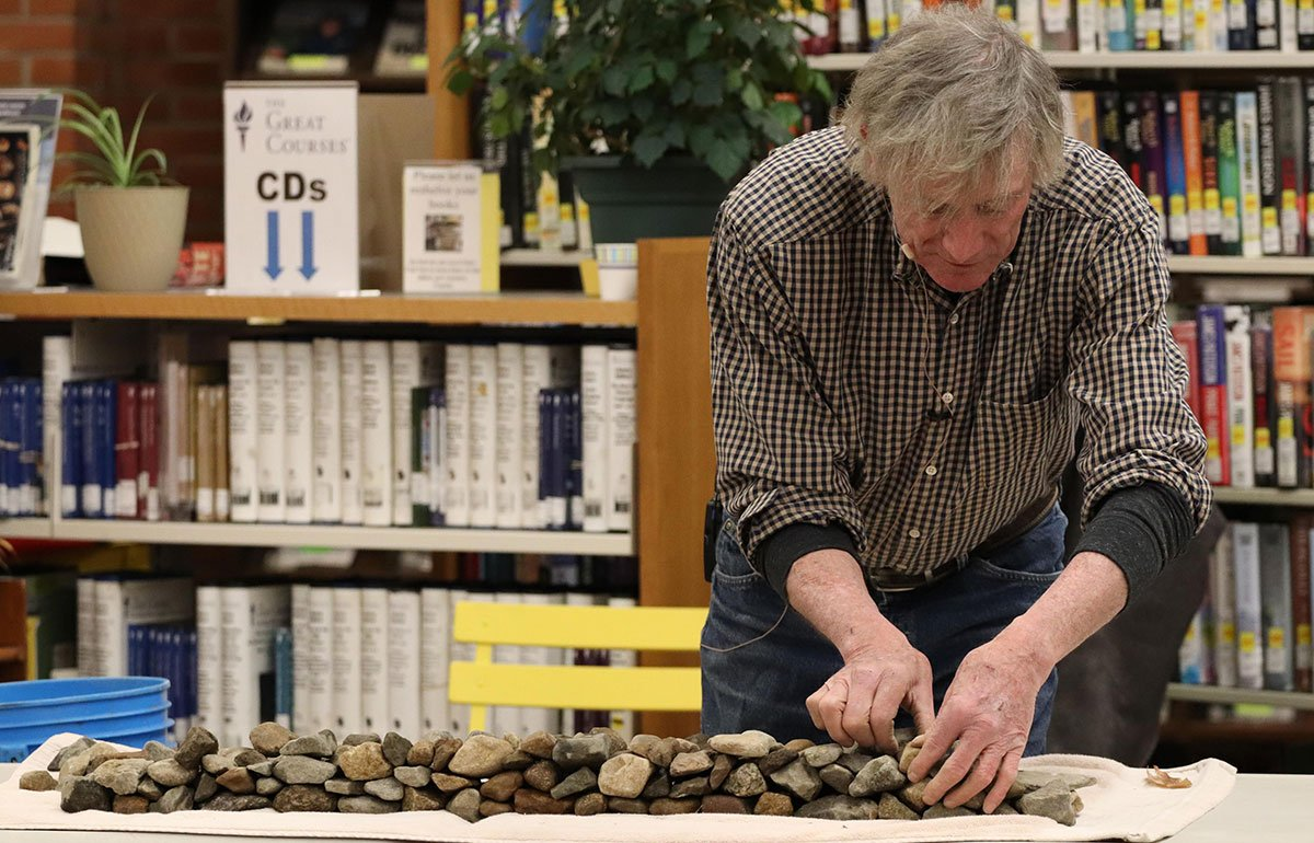 builder Kevin Gardner constructing a minature stone wall in a library