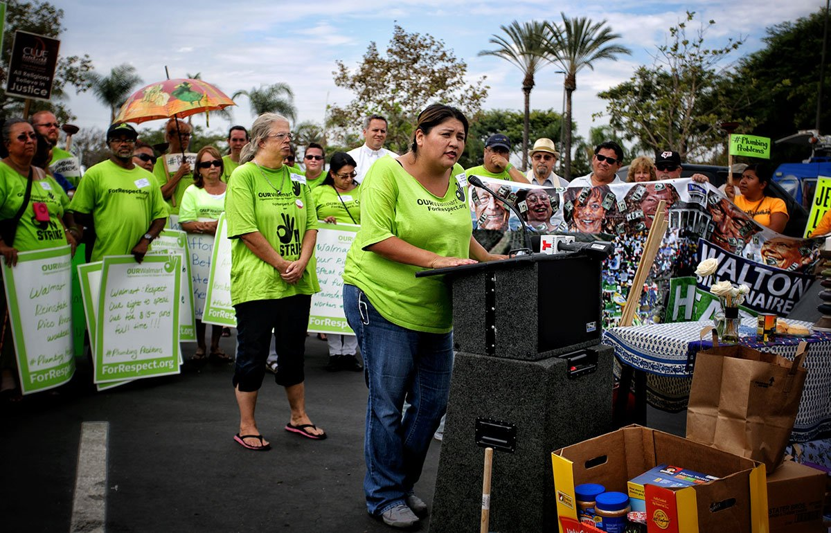 Woman in green shirt at podium surrounded by protesting workers